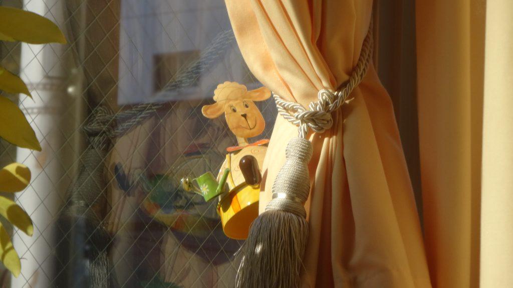 カーテンの脇にある羊さんの人形