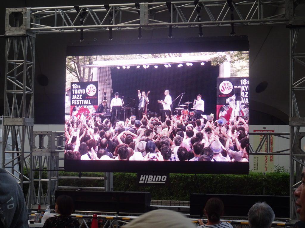 スクリーンに映し出された野外ステージでの演奏の様子