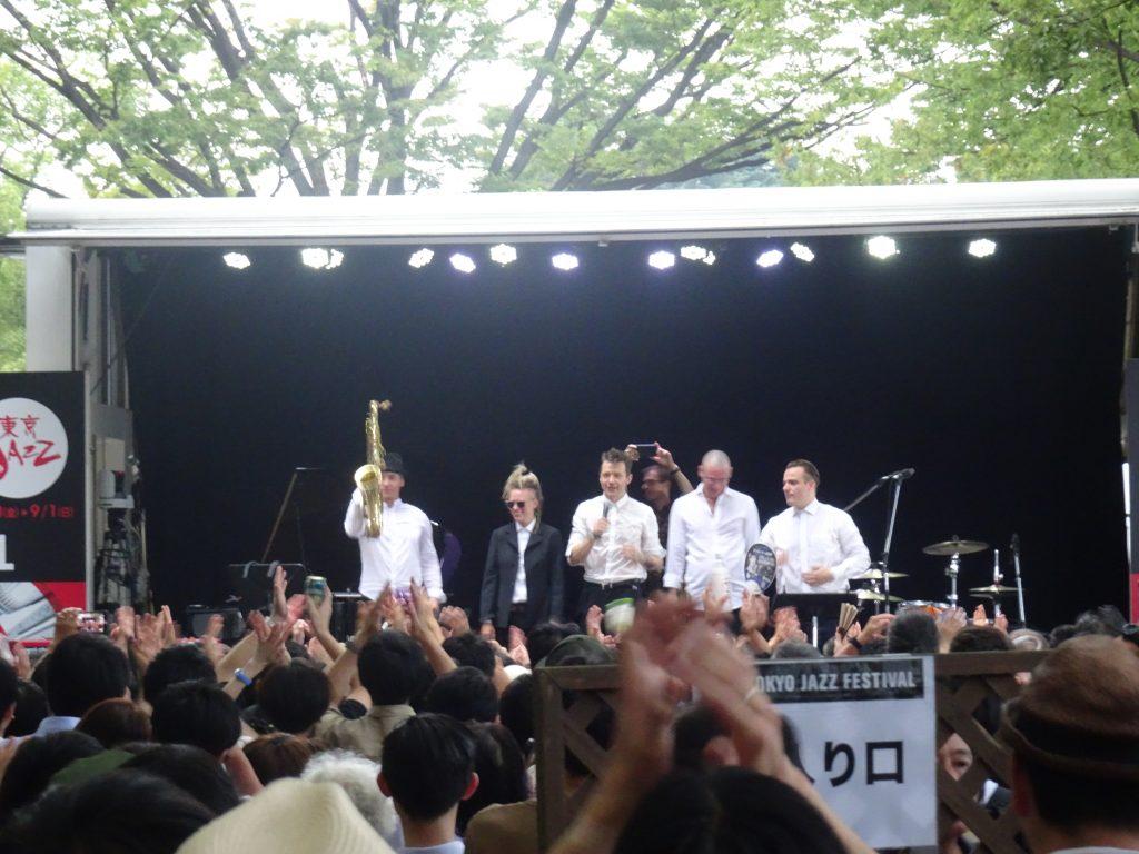 野外ステージの前でビールを飲みながら演奏を聴く人たち