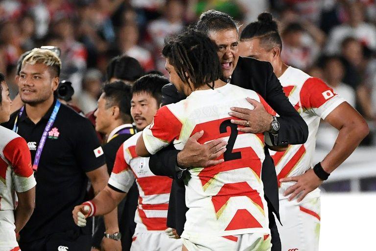 ピッチ上で堀江と抱きあうジェイミーヘッドコーチ