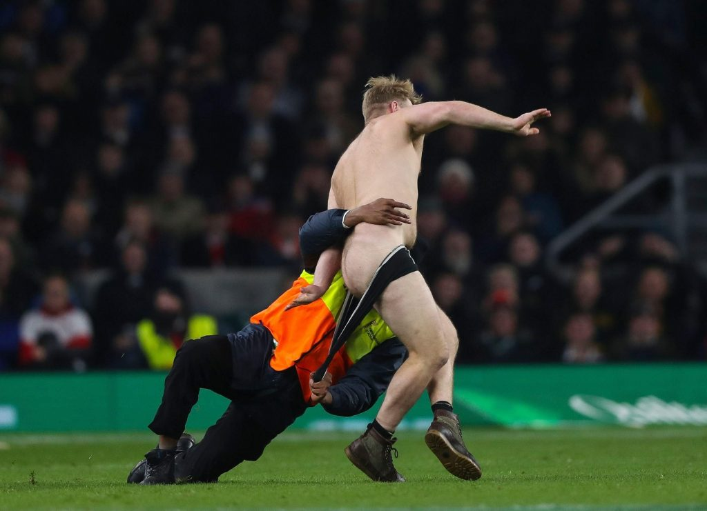 半裸の乱入者のパンツを引っ張る係員