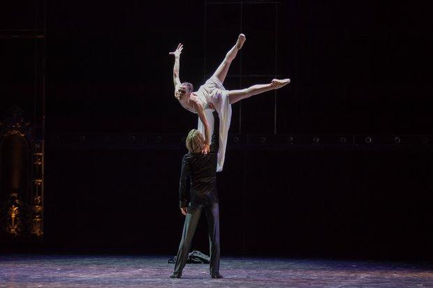 女性ダンサーを高くリフトする男性ダンサー