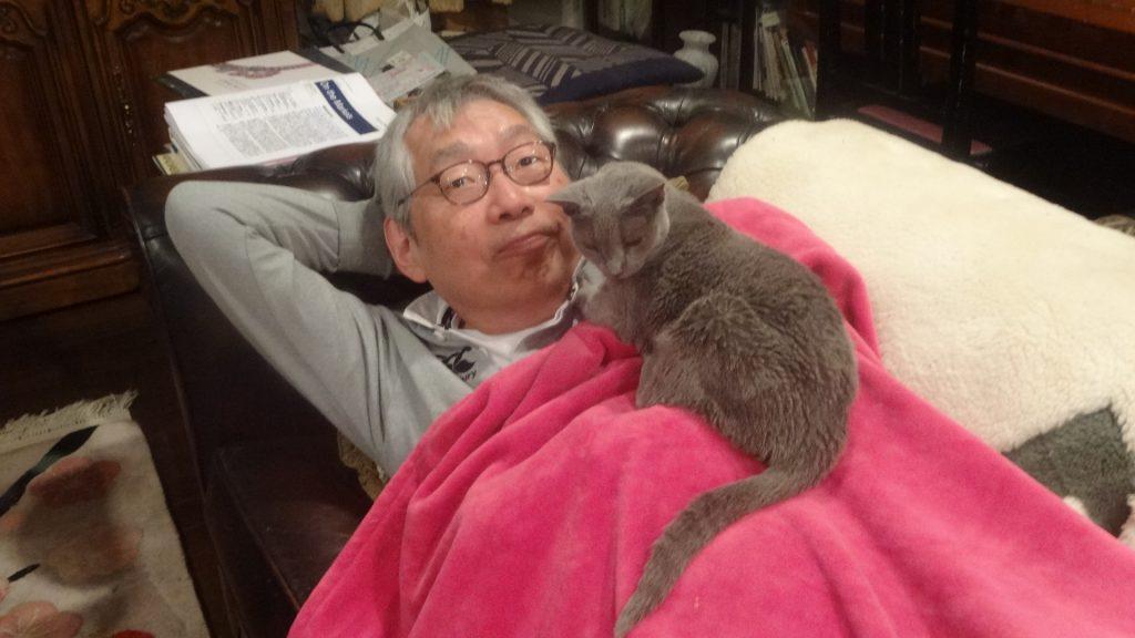ソファの上で毛布をかけて寝る書き手の上に乗るデイジー
