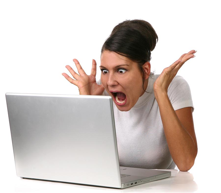 コンピューターに向い大げさな表情をする人
