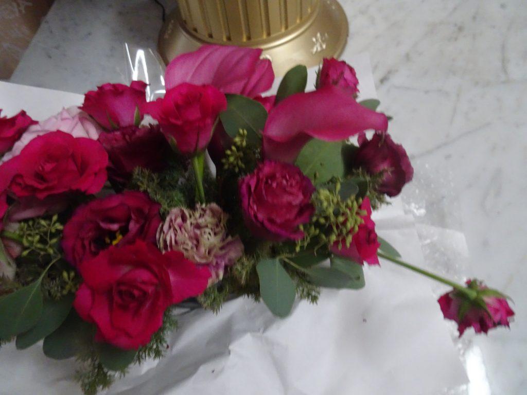 アレンジメントから1本だけ引っ張り出された赤いバラの花